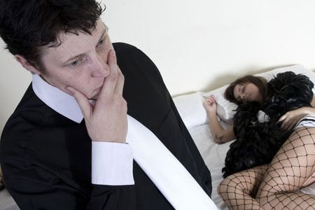 Man stressing about situation with prostitute on the bed behind him