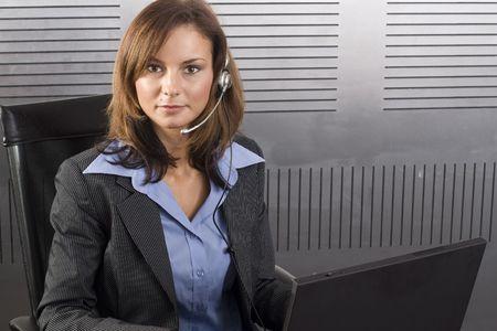 call center agent: Attraente giovane bruna call center agent parlando l'auricolare in un moderno ufficio di impostazione con portatile  Archivio Fotografico