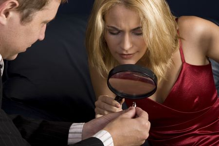 Blond woman inspecting diamond size with magnifying glass prior to accepting proposal Stock Photo - 2460260