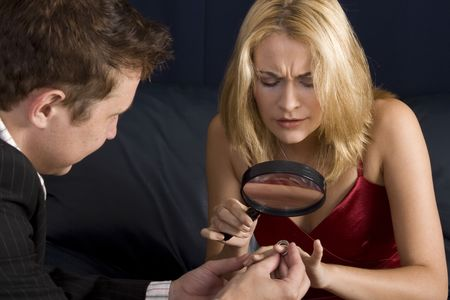 prior: Blond woman inspecting diamond size with magnifying glass prior to accepting proposal