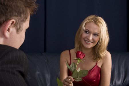 anniversary sexy: Man giving rose as gift to a beautiful blond girl who is smiling