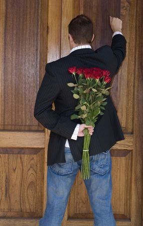 door man: Man knocking on door to present flowers to his date on valentines day