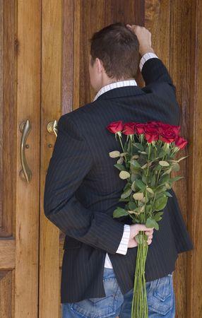 tocar la puerta: El hombre golpeando a la puerta de presentar flores a su fecha en el Día de San Valentín  Foto de archivo