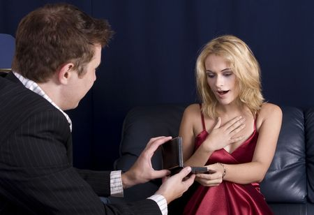 Man holding out necklace in box to a beautiful young blond girl while Stock Photo - 2482672