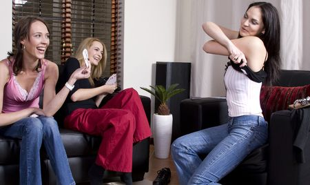 Three attractive girls playing strip poker at home