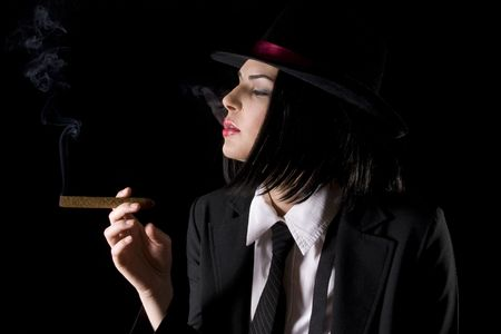 cigar smoking woman: Attractive brunette dressed as a new york gangster with black background