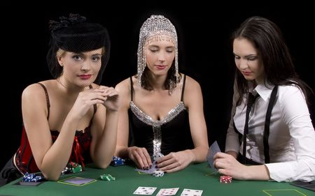 Three attractive girls dressed in moulin rouge clothing playing cards at green poker table photo
