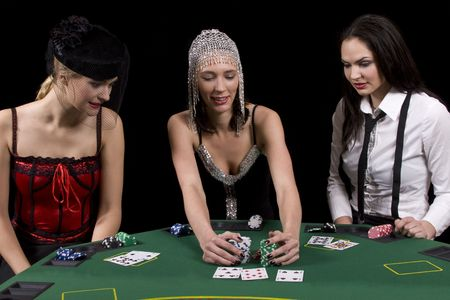 Three attractive girls dressed in moulin rouge clothing playing cards at green poker table Stock Photo - 3488570