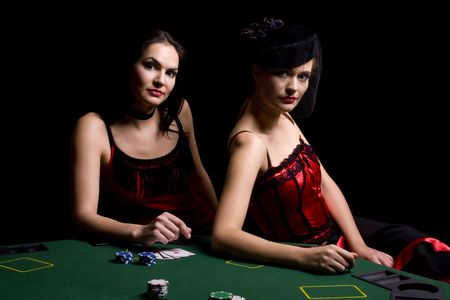Two attractive woman playing poker and at the casino wearing red dresses photo