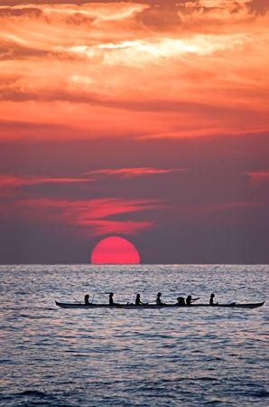 Hawiian women paddling a canoe home at sunset. Stock Photo