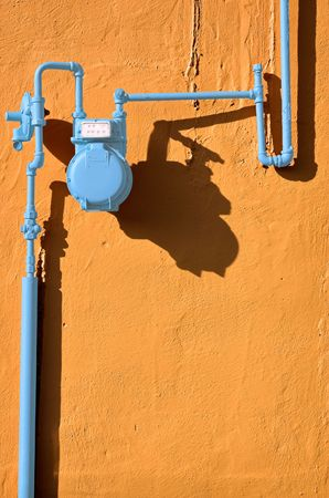 Blue gas meter against a terracotta wall