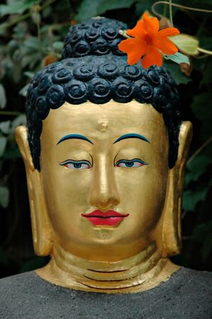 Statue of a Buddha with a red flower. Stock Photo