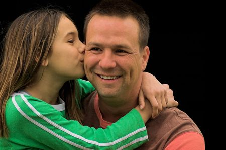 A young girl giving her father a kiss on the cheek.