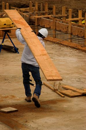 A construction worker carrying a very large board Stock Photo