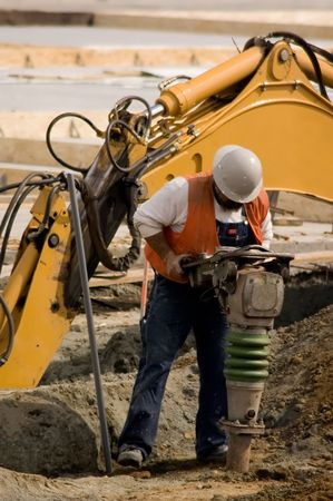 A construction worker using a large soil tamping machine