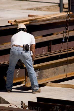 A construction worker handling an iron beam Stock Photo