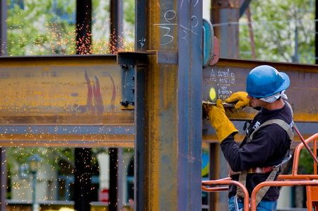 A construction worker welding an iron beam photo