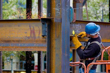 A construction worker welding an iron beam Stock Photo