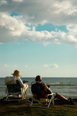 A retired couple at the beach, relaxing and reading at the end of the day.
