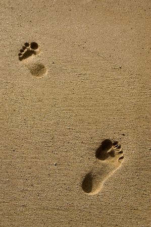 Two footprints in the soft sand of a Maui beach. photo