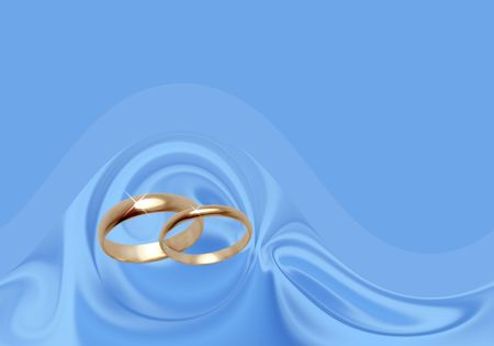 Wedding rings on blue material. Background for the invitation and congratulations wedding cards photo