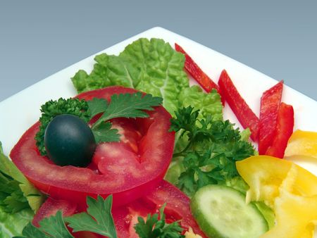 Dietic salad with olive on white plate