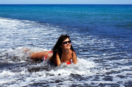 The beautiful girl in the sea on a black beach of island Santorini  Greece photo