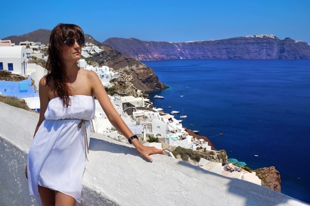 thira: Happy young woman on holidays, Santorini Thira town view