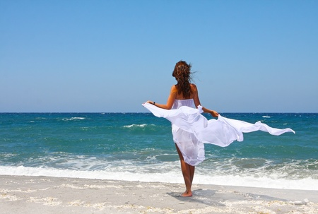 The beautiful girl at the sea in white developing clothes on a sea-breeze photo