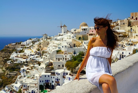 Beautiful woman on holidays, Santorini. Oia town view photo