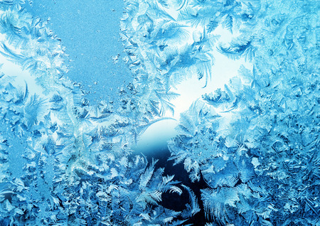 Frosty winter pattern at a window glass, macro texture photo