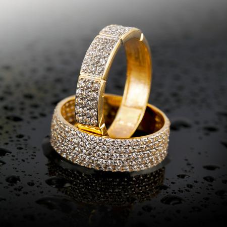 Golden jewelry wedding rings on black background   Stock Photo