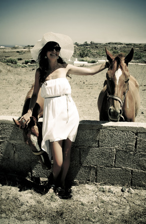 Happy young woman with horses on holidays in Greece photo
