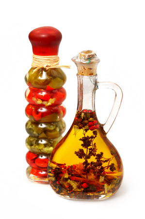 Olive oil with herbs, spices and seasonings in small bottle isolated over white background photo
