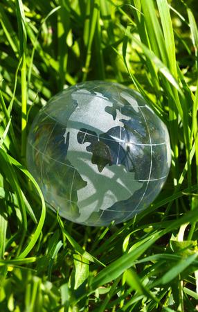 bionomics: Glass Globe Earth in green spring grass Stock Photo