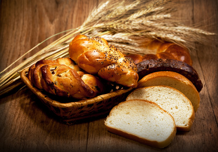 traditional goods: Fresh baked traditional bread with wheat in basket on wooden table    Stock Photo