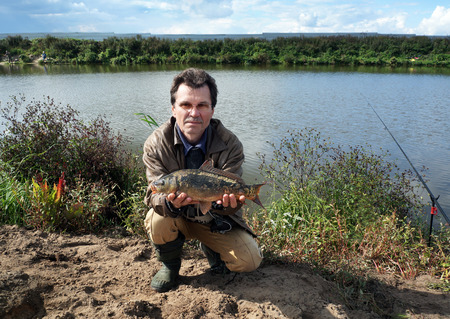 mirror carp: Fisherman With fish Mirror Carp. Fishing on river