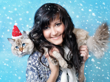 Charming young woman with siberian cat  in santa cap in snow photo