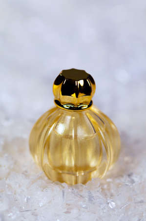 goldy: Perfume in golden color on white snow background