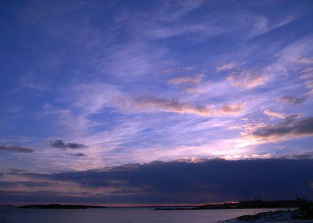 Mar de la puesta del sol. Cielo azul y nubes de color rosa  Foto de archivo