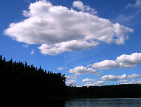 White clouds above wood lake Stock Photo