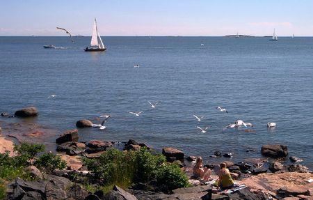 Landscape - sea, beach, stones, sail and sky Stock Photo