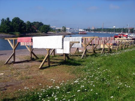 Pobladores lavar la casa alfombras en el mar y seco en el muelle de su ciudad de Helsinki