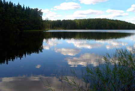 Las nubes blancas est�n flotando en agua del lago de madera