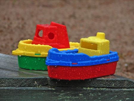 Toy ships left in the rain in a childrens sandbox photo