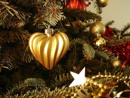 The gold heart hangs on a Christmas tree    photo