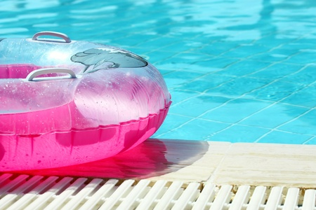 pink dolphin: Pink inflatable round tube in swimming pool Stock Photo