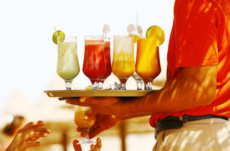 Waiter serving drinks  cocktails on the beach Stock Photo