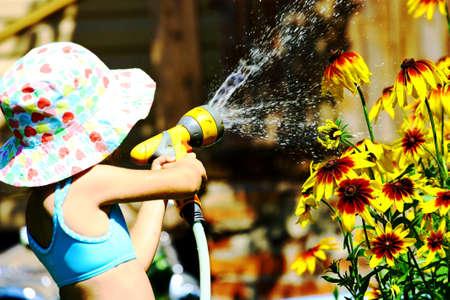 Little girl in summer hat watering yellow flowers