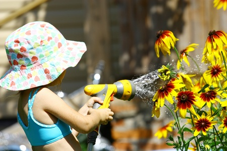 Little girl in summer hat watering yellow flowers photo